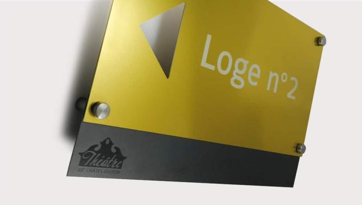 Ensemble signalétique de théâtre réalisée en gravure laser sur aluminium anodisé or et contre-plaque inox avec logo imprimé