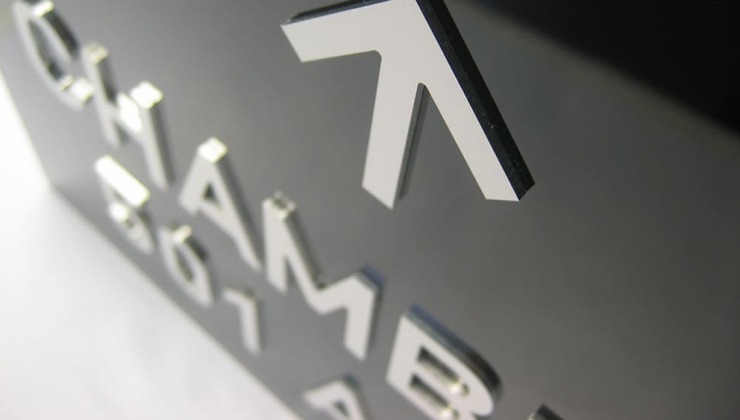 Découpe mécanique de lettres en métal contre-collées sur support en plexiglas noir